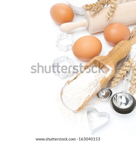 scoop with wheat flour, rolling pin, eggs and cookie cutters isolated on white - stock photo