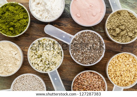 scoops of superfood - healthy seeds and powders (white and brown chia, brown and golden flax, hemp, pomegranate fruit powder, wheatgrass, hemp and whey protein, maca root) - top view - stock photo
