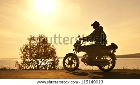 Scooter standing on a hill in the sunset - stock photo