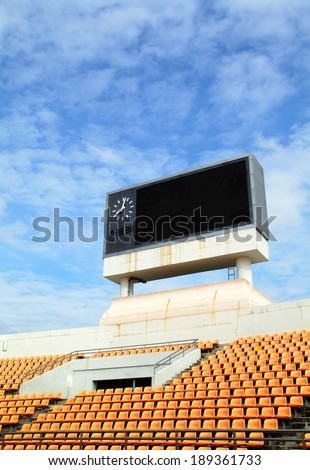 Scoreboard orange seat in stadium over cloud and blue sky background - stock photo