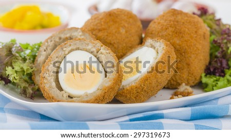 Scotch Egg - Hard-boiled egg wrapped in sausage meat, coated in breadcrumbs and deep-fried. Served with salad and piccalilli. - stock photo