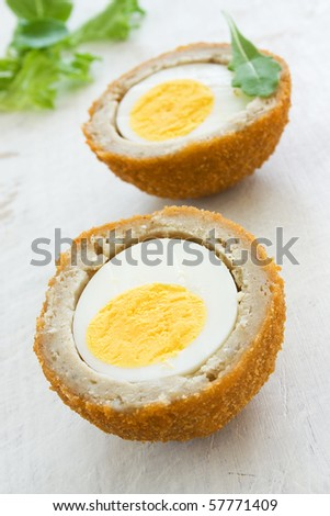 Scotch egg on a white board with green salad - stock photo
