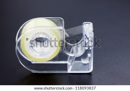 Scotch tape on black desk - stock photo