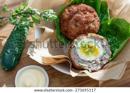 Scottish eggs on craft paper garnish with sauce and pickle cucmber - stock photo