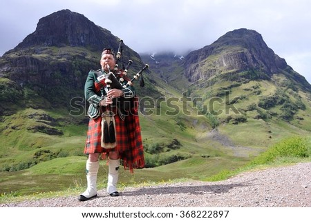 SCOTTISH HIGHLANDS - JUNE 15: Piper in traditional Scottish outfit plays on bagpipes in somewhere in Scottish Highlands, United Kingdom on June 15, 2013. - stock photo