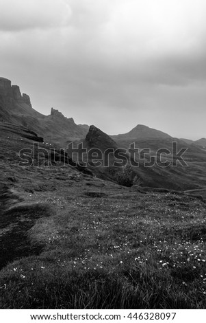 Scottish landscape at the Quiraing, Isle of Skye with a grassy meadow and hills, mountains and peaks covered by an overcast sky and a dark, gloomy black and white look - stock photo