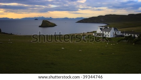 Scottish old house at sea shore with sheep on green field in evening ambiance, Isle of Skye, Scotland - stock photo