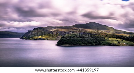 Scottish Seascape With Hill And Long Exposure Clouds With Little House In Background During Sunset Artistic Look - stock photo