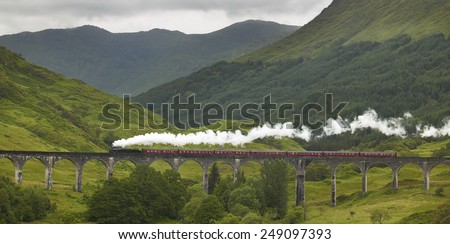 Scottish steam train passing a classic bridge. Horizontal - stock photo