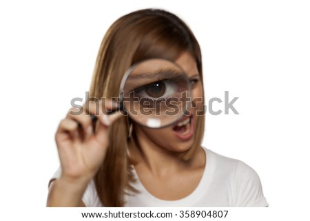 scowling young woman looking through a magnifying glass - stock photo