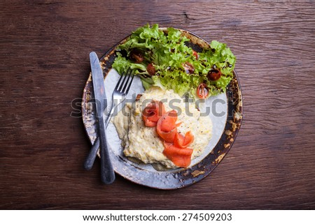 Scrambled egg and smoked salmon on wooden - stock photo