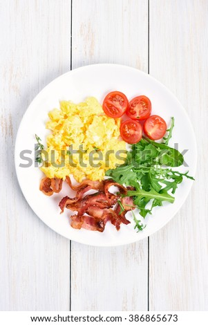 Scrambled eggs, bacon and vegetable salad on plate, top view - stock photo