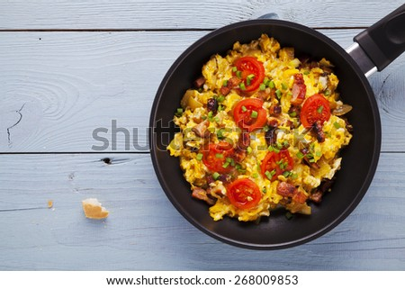 Scrambled eggs in a pan with bacon, onion and tomatoes sprinkled with chives, prepared from small farm eggs. - stock photo