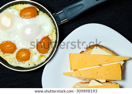 Scrambled eggs in the frying pan and sandwiches. - stock photo