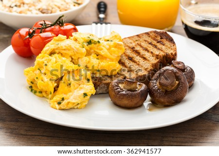 scrambled eggs on rustic toast with mushrooms. - stock photo