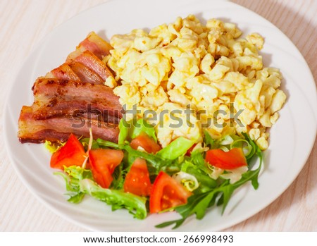 scrambled eggs with bacon and salad - stock photo