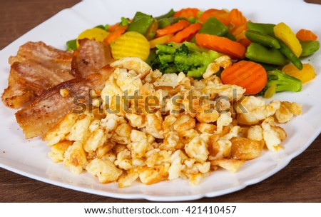 scrambled eggs with bacon and vegetables mix in a plate on wooden table - stock photo