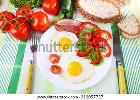 Scrambled eggs with bacon and vegetables served on plate on fabric background - stock photo