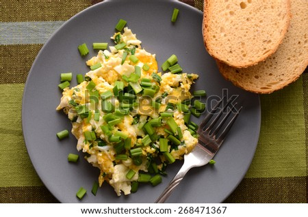 Scrambled eggs with fresh chives - stock photo