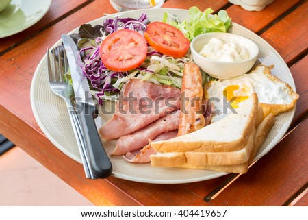Scrambled eggs with fried bacon, fried sausages, grilled tomato   - stock photo