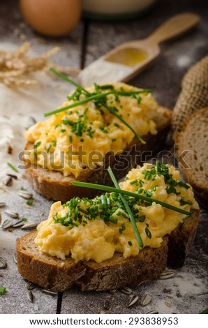 Scrambled eggs with herbs on wheat-rye crispy bread, homemade - stock photo
