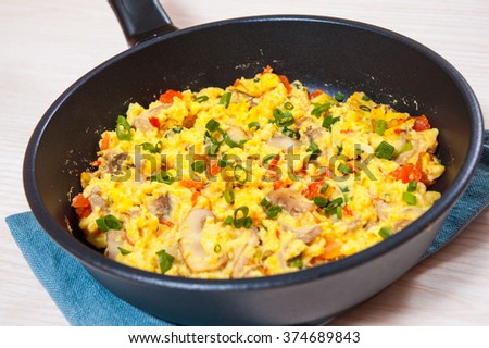 scrambled eggs with mushrooms and vegetables in a frying pan - stock photo
