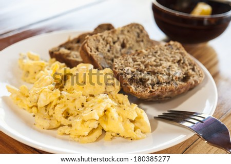 Scrambled Eggs with pepper and banana bread on a white plate - stock photo