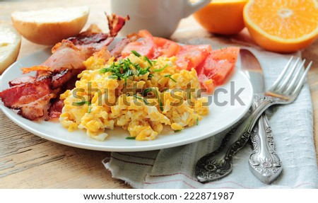 Scrambled eggs with tasty bacon and fresh tomatoes - stock photo