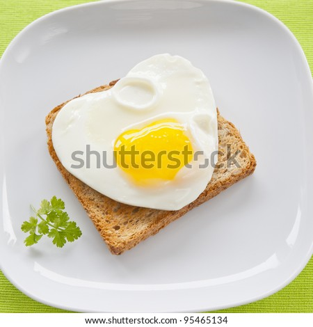 Scrambled eggs with toast on a white plate on a green cloth, framing square - stock photo