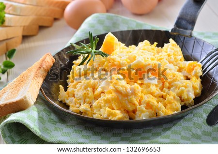 Scrambled eggs with toast, served in a pan - stock photo
