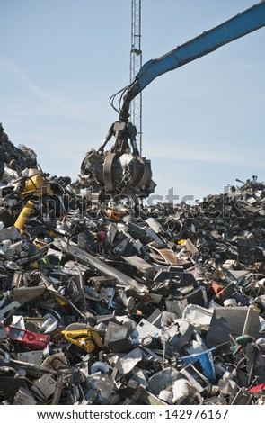 Scrap metal, iron and computer dump with crane. - stock photo