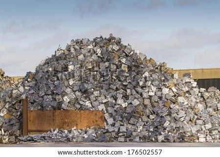 Scrap yard with pile of cars crushed into small cubes - stock photo