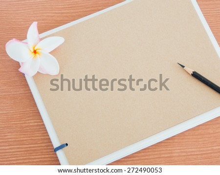 Scrapbook or Sketch book with black pencil on wood background, Flower top, Beauty design concept - stock photo