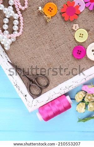 Scrapbooking craft materials and wooden frame with sackcloth inside on color wooden background - stock photo