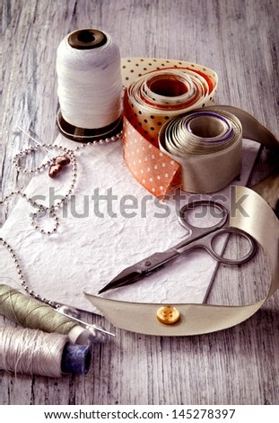 Scrapbooking craft materials/Backgroun d with sewing tools and colored tape/Sewing kit. Scissors, bobbins with thread and needles on the old wooden background - stock photo