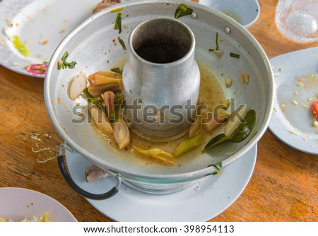 Scraps of food left in soup pot plastic dish on table. - stock photo