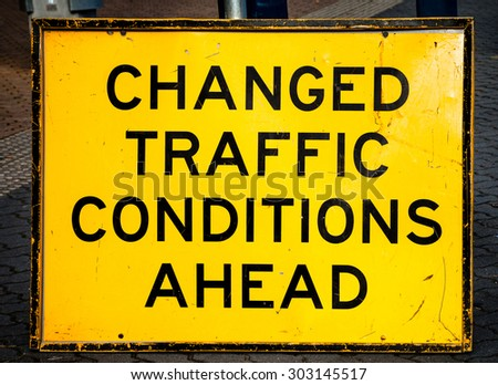 Scratched and damaged yellow and black temporary street sign warning CHANGED TRAFFIC CONDITIONS AHEAD - stock photo