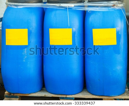 Scratched blue barrels packed with white labels Chemical Plant - stock photo