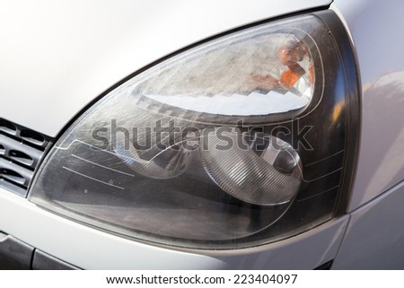 Scratched car headlight - stock photo