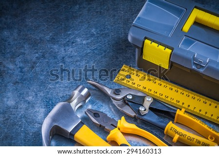 Scratched metallic background with toolbox hammer ruler pliers and tin snips construction concept. - stock photo