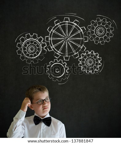 Scratching head thinking boy dressed up as business man with chalk turning gear cogs or gears on blackboard background - stock photo