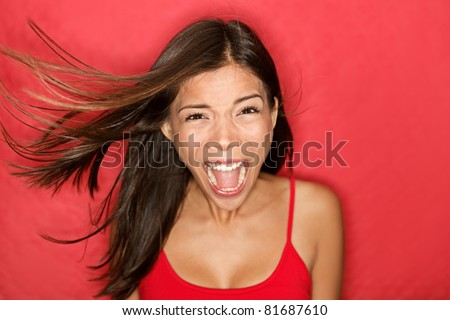 Scream. Woman screaming wild and crazy at full energy looking at camera on red background. Beautiful mixed race Asian Caucasian brunette female model with wind in the hair. - stock photo