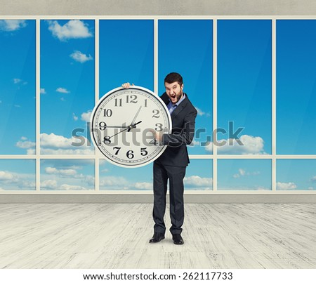 screaming angry businessman with big clock in room with windows - stock photo