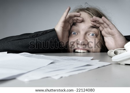 Screaming businessman hiding under the desk from the crisis - stock photo