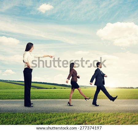 screaming businesswoman in formal wear commanding her subordinates at outdoor - stock photo