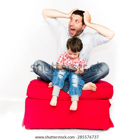 Screaming father angry because his baby is playing with smartphone on a red sofa - isolated on white background - stock photo