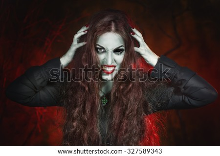 Screaming halloween beautiful vampire with long hair in hell - stock photo