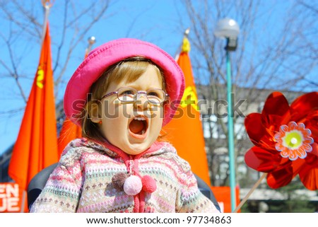 Screaming little girl 2 years old wearing glasses in pink hat and red flags - stock photo