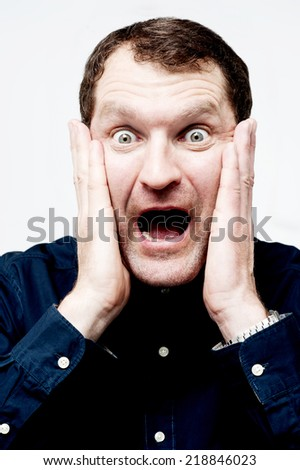 Screaming middle aged man covering his ears - stock photo