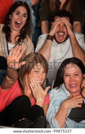 Screaming people curled up in seats at a movie theater - stock photo